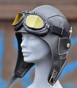 balck leather aviator hat with goggles displayed on a model