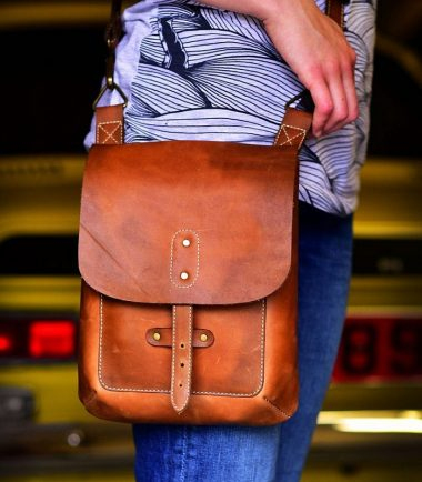brown leather cross body bag close up worn on a model